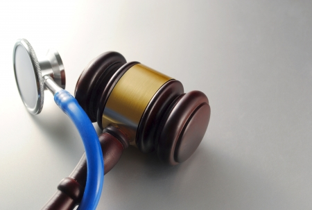 brown gavel and a medical stethoscope on gray background Stock Photo - 17163500