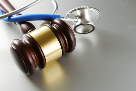 brown gavel and a medical stethoscope on gray background