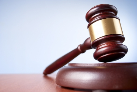 justice court: brown gavel with a brass band on a blue background Stock Photo