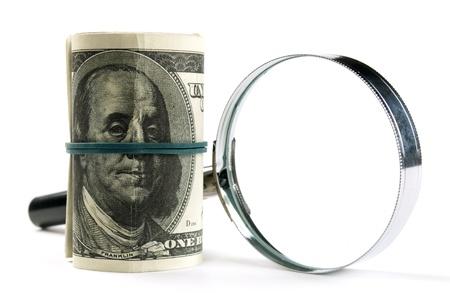 dolar: Dólares americanos enrollado y lupa sobre un fondo blanco