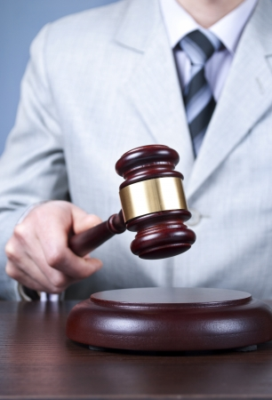 gavel in the hand of a man in a business suit Stock Photo