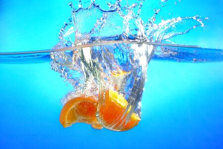 Orange falls into the water and making splashes Stock Photo - 17467113