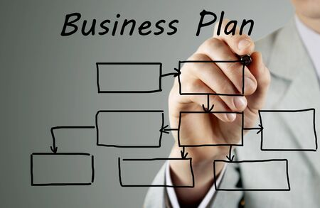 process flow: man in a business suit makes a block diagram on a blackboard Stock Photo