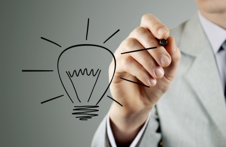 Businessman draws a light bulb, the symbol of the idea of Stock Photo - 18540415