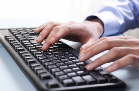 Businessman typing on a computer keyboard photo