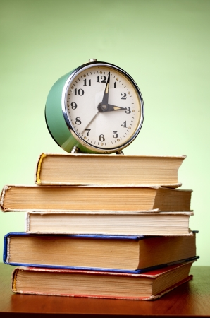 school things: stack of books and an alarm clock, as well copyspace for your text Stock Photo