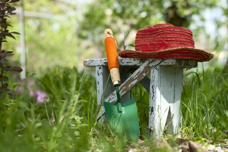 household chores: garden shovel, a bench and a hat on a bed of green plants Stock Photo