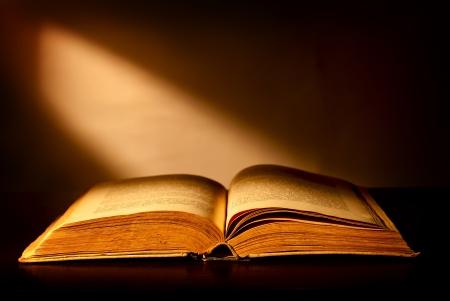 libros abiertos: Antiguo libro abierto y un haz de luz incidente