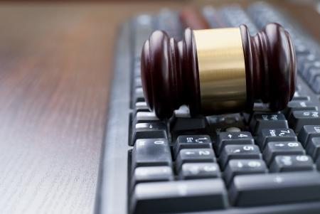 derecho penal: martillo y teclado de la computadora, la imagen conceptual Foto de archivo