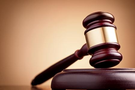 martillo juez: martillo marr?n sobre la mesa en un fondo marr?n