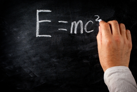 student writing on the chalkboard Einsteins formula e=mc2 photo