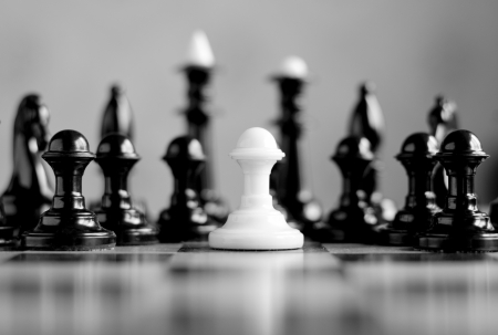competitors: white pawn surrounded by black chess pieces on a chess board Stock Photo