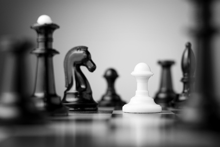 white pawn surrounded by black chess pieces on a chess board Stock Photo