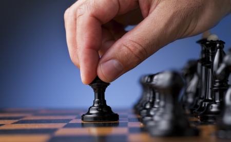 Schachspiel, Schachspieler macht eine Bewegung der schwarzen Bauern nach vorne