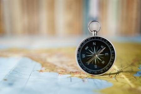 Kompas op de kaart en het boek in de achtergrond op het gebied van verwarring Stockfoto - 20736304