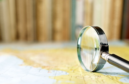 a round of inspection: magnifying glass on the map and book in the background in the area of confusion