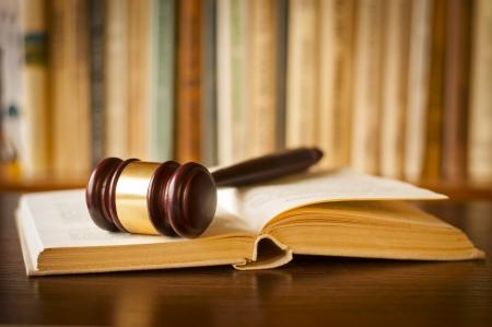 法廷や法律執行機関の事務所のページ上で休んでいる裁判官の小槌を持つオープン法の本 写真素材