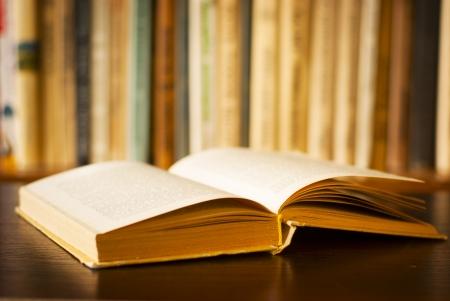 Faible angle de vue d'un grand livre relié ouvert allongé sur un bureau en bois devant une étagère de livres avec peu ddl