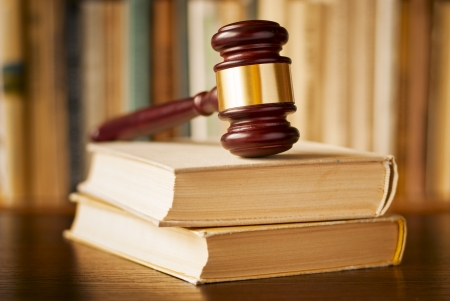 ruling: Law books with a wood and brass judges gavel resting on top on a wooden desk, closeup view with shallow dof