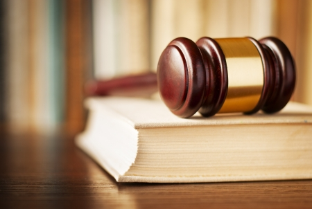ruling: Conceptual image of law enforcement, justice and sentencing with a closeup view of a wooden judges gavel lying on a law book