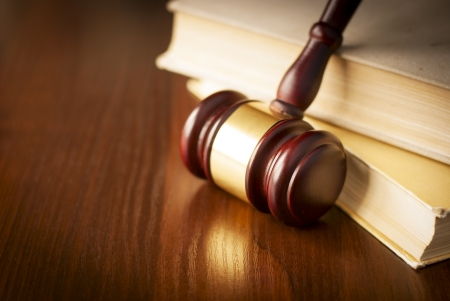 sentencing: Wooden gavel in a courtroom standing upright against a stack of law books on the judges desk