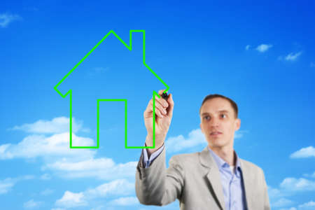 ownership equity: Conceptual image of a stylish young business man drawing the outline of a house in the blue sky with a green marker