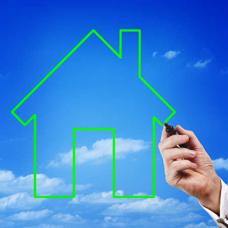 ownership equity: Conceptual image of the hand of a man drawing the green outline of an eco house in the blue sky with a marker Stock Photo
