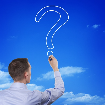 Conceptual image of a young man with his back to the camera drawing the outline of a question mark in the blue sky photo