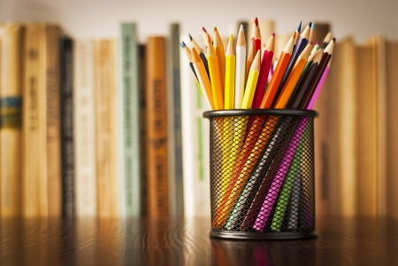 desk tidy: Wire desk tidy full of coloured pencils standing on a wooden table in front of a bookshelf full of books with shallow dof and copyspace