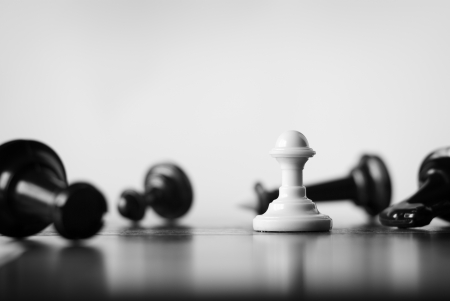 Single white pawn on a chess board surrounded by a number of fallen black chess pieces with selective focus