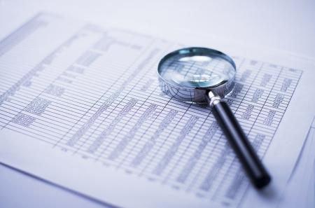 Estados financieros, documentos y lupa sobre un escritorio de oficina Foto de archivo - 21615821