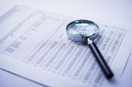 financial statements, documents and magnifier on an office desk Stock Photo