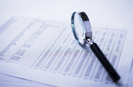 financial statements: financial statements, documents and magnifier on an office desk Stock Photo