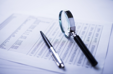 financial statements, documents, dollars, magnifying glass and pen on office desk Stock Photo
