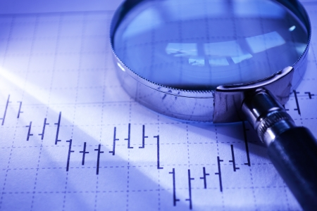 statistical: Magnifying glass lying on an statistical graph conceptual of research, investigation and analysis