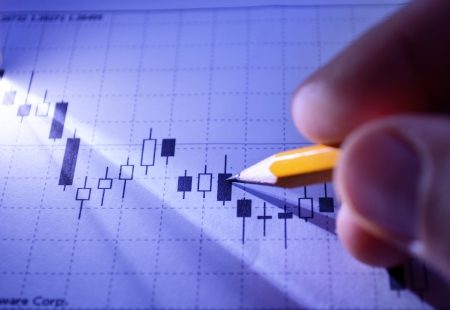 analyses: Man working on business planning and strategy with a close up view of his fingers holding a pencil as he analyses a graph