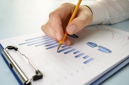 shirtsleeves: Close up view of the hand of a young business man in shirtsleeves holding a pencil working on a bar graph