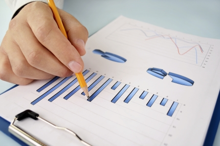 statistical: Close up view of the hand of a young business man in shirtsleeves holding a pencil working on a bar graph