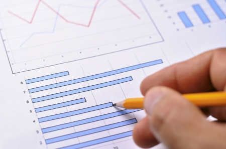 statistical: Close up view of a male hand holding a pencil analysing a fluctuating bar graph showing business performance