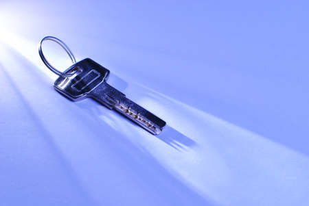 accession: Conceptual image of a silver metallic security key lying in a shaft of light across a blue surface with copyspace Stock Photo