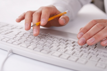 enters: Man typing on a computer keyboard at work holding a pencil in the fingers of one hand as he enters data, close up view