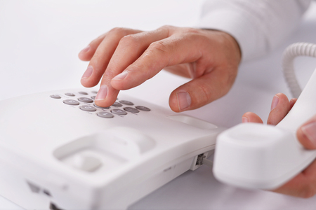 telephone call: Close up view of the hands of a man making a telephone call on a landline holding the handset close to the camera and dialling in the number on the keypad with the other hand Stock Photo