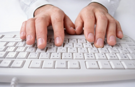 shirtsleeves: Close up of the hands of a man in shirtsleeves typing on a white computer keyboard entering business data Stock Photo