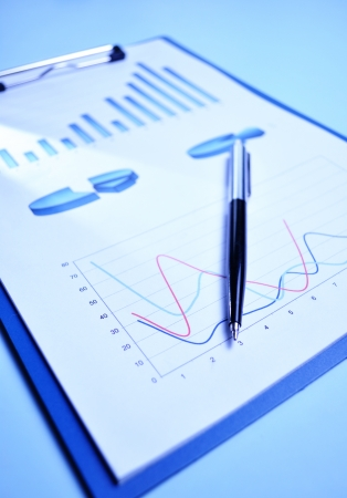 analytical: Document showing a bar graph, pie graphs and a fluctuating chart depicting business performance, planning, projections and strategy