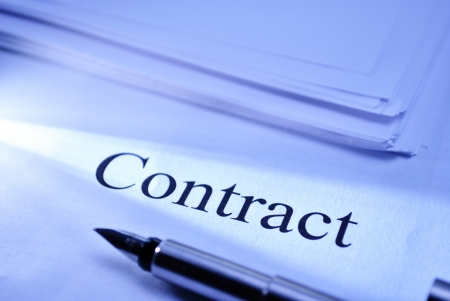 contractual: Pen lying on a document headed Contract conceptual of a legal binding business contract or partnership