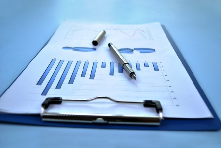analytical: Low angle close up view of a clipboard with analytical bar and pie graphs and a pen lying on top depicting business planning and strategy