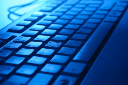 alphanumeric: Close up background of a computer keyboard in blue light with alphanumeric keys and functions for entering data Stock Photo