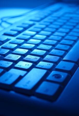 function key: Close up background of a computer keyboard in blue light with alphanumeric keys and functions for entering data Stock Photo