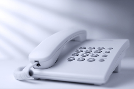 telephonic: Low angle view of a white office dial up landline or terrestrial telephone with handset and keypad for telephonic communication Stock Photo
