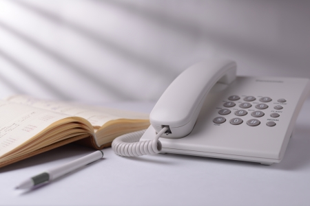 landline phone: Landline dial up telephone with an open note book or phone directory and pen alongside on a white background with shadow effect Stock Photo